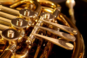 close up of brass french horn on black