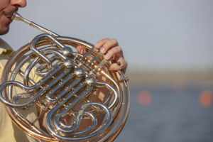 man playing french horn with water behind