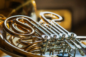 close up of french horn on side with valves showing