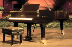 grand piano on stage with highlighted casters or wheels