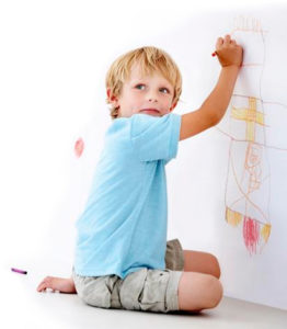 little boy drawing with crayon on wall