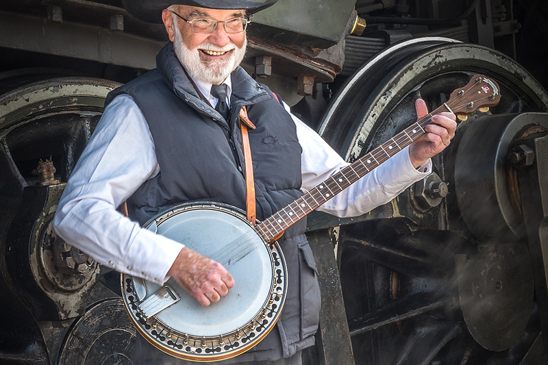 Playing banjo with train behind