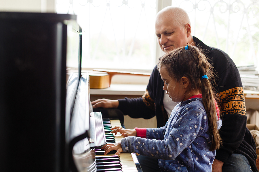 Home piano lesson with young girl, older man