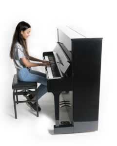 teen playing upright piano