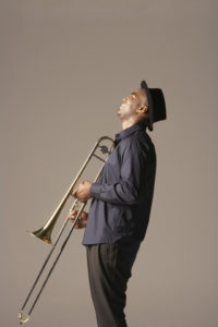 man holding trombone, side view