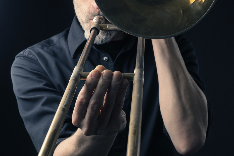 man playing old trombone, viewed from front